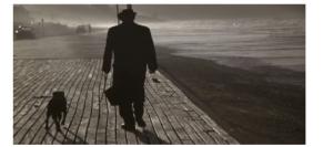 Старик с собакой, гуляющий по знаменитому деревянному настилу пляжа в Довиле
